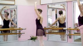 In dancing hall, Young ballerina in purple leotard performs elegantly a certain ballet exercise, grand battement back. Standing near barre at mirror in ballet stock video footage