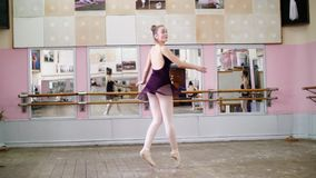 In dancing hall, Young ballerina in purple leotard performs tour jete en dedans, She is moving through the ballet class. Elegantly stock footage