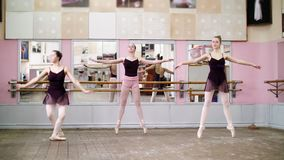 In dancing hall, Young ballerinas in black leotards perform pas echappe, standing on toes in pointe shoes near barre at. Mirror in ballet class stock video footage