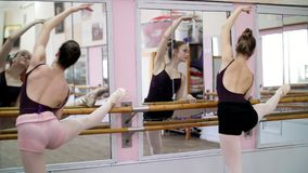 In dancing hall, Young ballerinas in black leotards stretching at barre, on pointe shoes, elegantly, standing near barre. At mirror in ballet class stock video