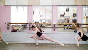 In dancing hall, Young ballerinas in black leotards are stretching parterre, standing near barre at mirror in ballet. Class stock footage