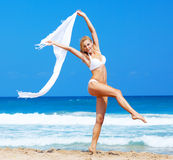 Dancing happy girl on the beach. Jumping & dancing happy girl on the beach, fit sporty healthy sexy body in bikini, woman enjoys wind, freedom, vacation Stock Images