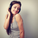 Dancing happy young woman listening the music from headphones. V Royalty Free Stock Photography