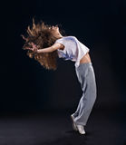 Dancing hip-hop. Beautiful girl dancing modern on black background Stock Image