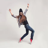 Dancing hipster girl in glasses and black beanie Royalty Free Stock Photos