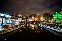 Dancing Houses and Boats at Damrak At Night in Amsterdam. The street was located on a rak reach, a straight part of the Amstel river near a dam.Former stock Royalty Free Stock Photography