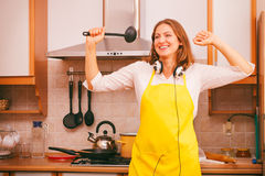 Dancing housewife in kitchen Stock Images
