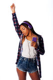 Dancing jamming listening to music. Beautiful teenager girl listening, dancing and jamming to music on mobile phone wearing purple headphones, on white Royalty Free Stock Photography