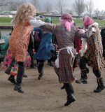 Dancing for joy. Group of folk dancer link rms in a circle and lep and dance, all men wearing colourful / colorful female costumes. Taken on the riverside at Ely stock photography