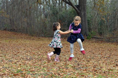 Dancing for Joy. Two friends dance for joy in the Autumn leaves in Arkansas.  They are holding hands and jumping high and running in circles Royalty Free Stock Photo