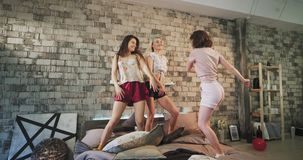 Dancing ladies in pajamas on sleepover party , have a fun time in a modern urban bedroom design , jumping over the bed stock video footage