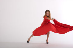 Dancing lady in red. Sexy lady in red dress in studio is dancing Stock Image