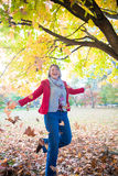 Dancing In the Leaves. A woman with arms wide dancing under falling leaves. The image orientation is vertical and there is space for copy Stock Image