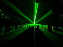 Dancing in the light. Silhouettes dancing in the night club against against the green laser rays Royalty Free Stock Photography