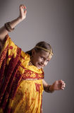 Dancing little girl in traditional Indian clothing and jewelerie Stock Photo