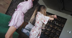 Dancing lovely beautiful ladies in pajamas in the morning enjoying the moment together in a large studio apartment with stock footage