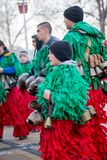 Dancing and making noise in ecstasy with several brass bells. PERNIK, BULGARIA - JANUARY 26, 2018: Teen boy dances and jumps in ecstasy with huge brass bells to Stock Photo