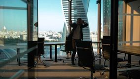 Dancing male businessman silhouette in modern business office with glass wall and door stock video