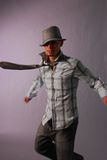Dancing male in plaid. Latino male  In black vest stripped shirt on green wearing a vintage hat dancing  slight blur Stock Photos