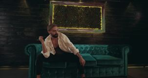 Dancing men with a bearded on the green velvet sofa with perfect choreography. Red Epic. Dancing men with a bearded on the green velvet sofa with perfect stock footage