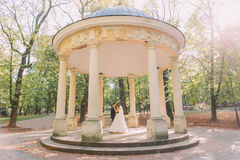 The dancing newlyweds in the old alcove placed in the sunny park. Royalty Free Stock Photography