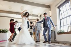 Dancing On Our Wedding Day. Newly wed couple are enjoying dancing with all of their guests on their wedding day royalty free stock image