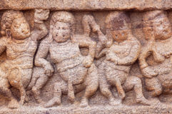 Dancing overweight people on stone relief of 7th century temple in Badami town, India. Royalty Free Stock Photo