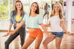 Dancing people. Beautiful young women in dance studio are posing and smiling to the camera Royalty Free Stock Photos