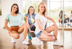 Dancing people. Beautiful young women in dance studio are posing and smiling to the camera Royalty Free Stock Image