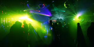 Dancing people - extreme wideangle picture. Coloured atmosphere with laser beams and disco-scanners stock image
