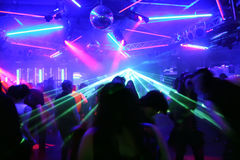 Dancing people in front of flashing laser beams. In an underground club royalty free stock images