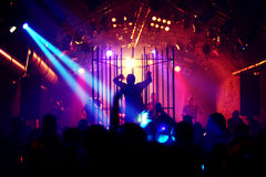 Dancing people/male dancer in a steel cage. Dancing people in an underground club Royalty Free Stock Photos
