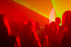 Dancing people in red and yellow laser light. Silhouettes of dancing people in red and yellow laser lights at nightclub Royalty Free Stock Photography