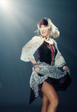 Dancing pirate. Glad lady in the Medieval pirate costume dancing indoors under the magic light royalty free stock image