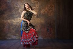 Dancing pretty woman in Indian costume on a textured background Stock Photography