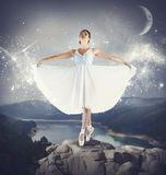 Dancing on a rock. Ballerina dancing on tiptoe above a rock Stock Photography