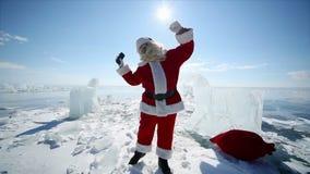 Dancing Santa Claus. Christmas holidays, Santa Claus walks around the lake Baikal, Siberia, Russia stock footage