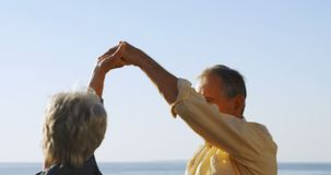 Dancing senior delle coppie alla passeggiata vicino al mare 4k archivi video