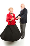 Dancing Seniors Spin. Beautiful senior lady spinning as she dances with her husband. Full body isolated on white Royalty Free Stock Images