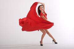 Dancing sexy lady. Sexy lady in red dress in studio is dancing Stock Photo