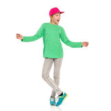 Dancing And Shouting Child Girl. Young girl in pink full cap, green blouse, jeans and sneakers standing with legs crossed and arms outstretched, looking away and Royalty Free Stock Images