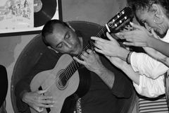 The flamenco guitarist plays the guitar and the girls clap their hands. Dancing and singing Flamenco in a bar in Sevilla, in Betis street, along the Guadalquivir royalty free stock photo