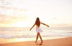 Dancing spensierato felice della donna sulla spiaggia al tramonto Fotografia Stock