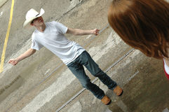 Dancing in Street. Young man dancing in a street to impress girl. Teen boy being silly to get a girls attention royalty free stock image