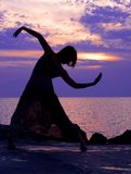 Dancing at sunset. Young woman standing at ballerina pose, sunset at the background royalty free stock image