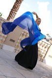 Dancing with swirling veil. Attractive blonde belly dancer in black with blue veil blowing in the wind behind her, looking at viewer Stock Photography