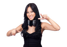 Dancing to the music. A young girl with DJ style headphones pointing her fingers and smiling Stock Image