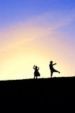 Dancing on top of the hill. Silhoutte of two little girls dancing on top of the hill against colorful sunset Stock Photo