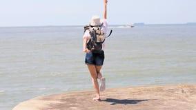 Dancing turistico della giovane donna felice sulla spiaggia video d archivio