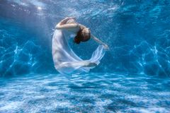 Dancing under the water. Girl shows the performance under the water, she dances in a white dress stock photos